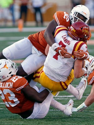 Iowa State quarterback Joel Lanning (7) is tackled by Texas' Malcolm Roach (32) and Jeffrey McCulloch (23) during the first half of an NCAA college football game, Saturday, Oct. 15, 2016, in Austin, Texas.