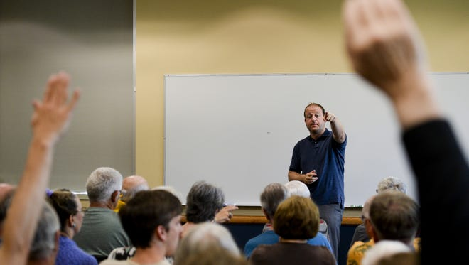 Citizens raise their hands with questions for U.S. Rep. Jared Polis, D-Colo., during a 2014 town hall meeting.