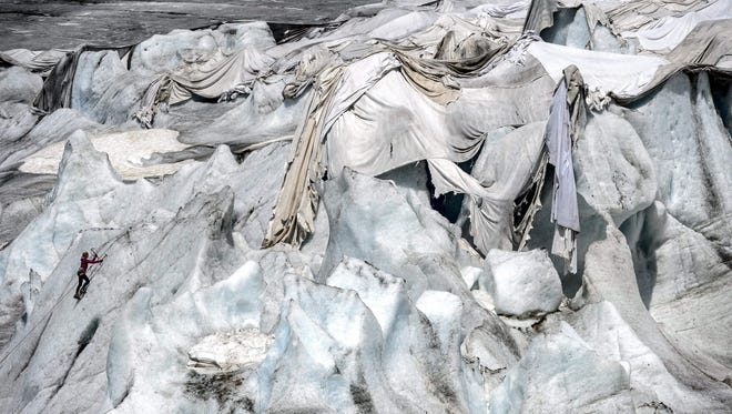 A woman practices ice climbing on July 14, 2015 next to insulating foams wrapping up the Rhone Glacier which has been shrinking under the summer sun near Gletsch.