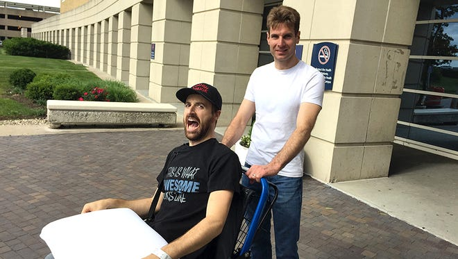 James Hinchcliffe is released from the hospital on Wednesday, May 27, 2015, helped by Will Power.