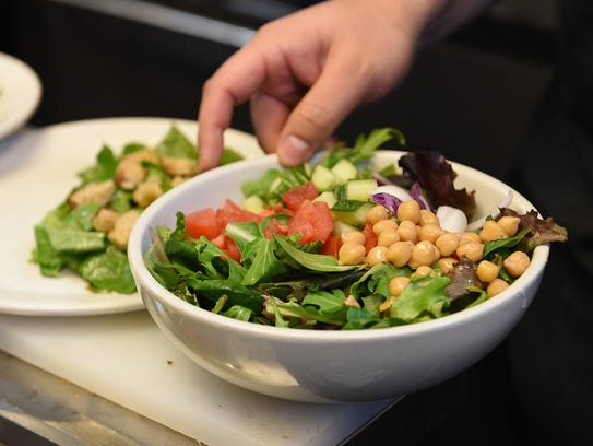 A salad is prepared at Restaurant 415 on Friday, January