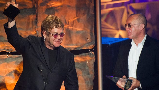 "Elton John, left, and Bernie Taupin accept the ""Johnny Mercer"" award at the Songwriters Hall of Fame 44th annual induction and awards gala in 2013 in New York. ELTONSONGS features the music of John and Taupin."