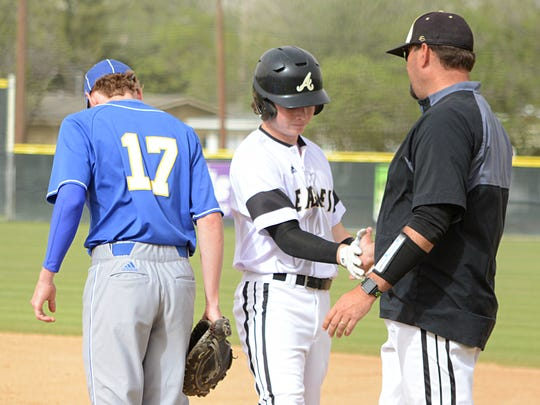 Abilene High's Ethan Flanders is greeted at first by his first-base coach after hitting an RBI single during the Eagles' 7-4 win over Lubbock Christian on Friday at Blackburn Field.