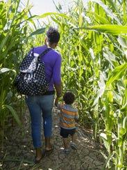 Karla Maki leads her son Grayson Maki, 22 months, through