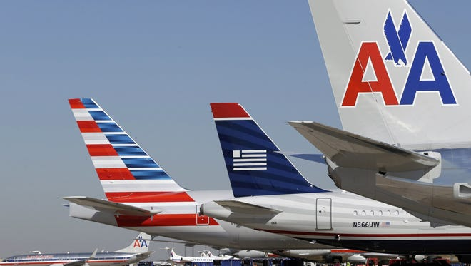 This file photo from Feb. 14, 2013, shows American Airlines and US Airways planes  at Dallas/Fort Worth International Airport.