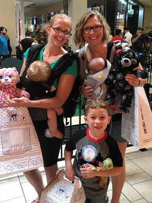 Sami Baca, from left, holding 10-month-old Audrey Baca, Ezra Barcelo, and Kara Barcelo, holding Kara, 7 weeks, were happy with their bears after waiting in line for five hours at Build-A-Bear in Cielo Vista Mall.
