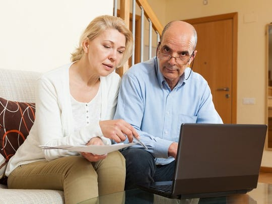 A mature married couple examining their finances on their laptop.