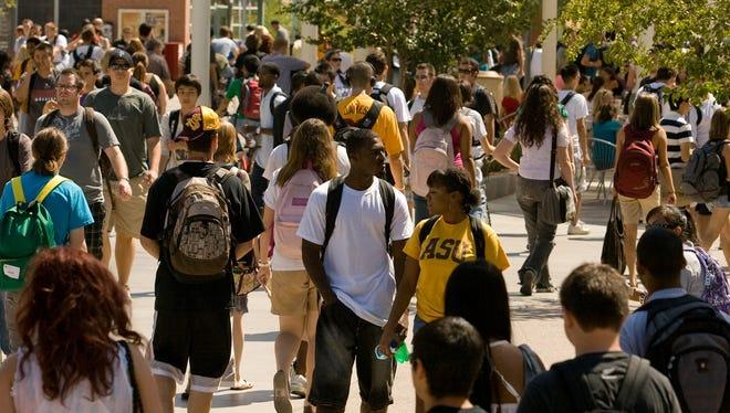 Students walk on the Arizona State University campus in Tempe, Ariz.