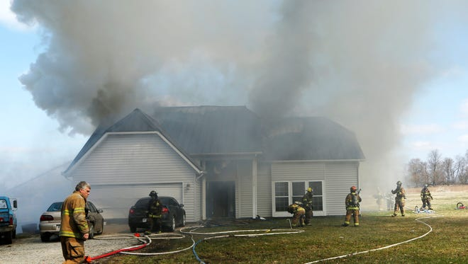 Firefighters battle a house fire Saturday, April 5, 2014, at 10790 Brandy Kay Court near Mulberry. Twin brothers Landon Tyler Abbott, 3, and Liam Cecil Abbott, 3, were in the house when Dep. Rob Rush, Dep. Shane Howard and Sgt. Andy Cree of the Tippecanoe County Sheriff's Office arrived on the scene. The boys, both unconscious, were removed from the house and transported to IU Health Arnett Hospital and St. Elizabeth East where they were later pronounced dead.