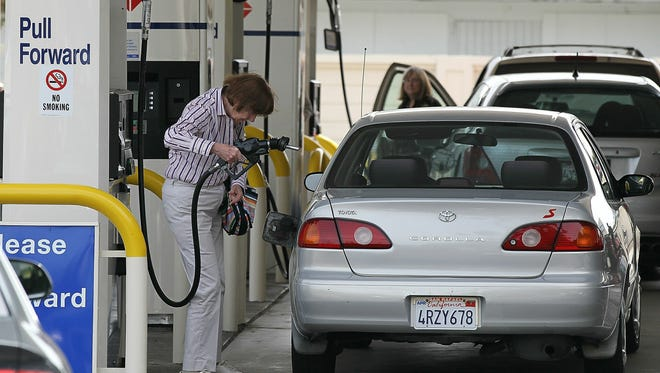 A customer prepares to pump gas into her car at an Arco gas station in Mill Valley, Calif.