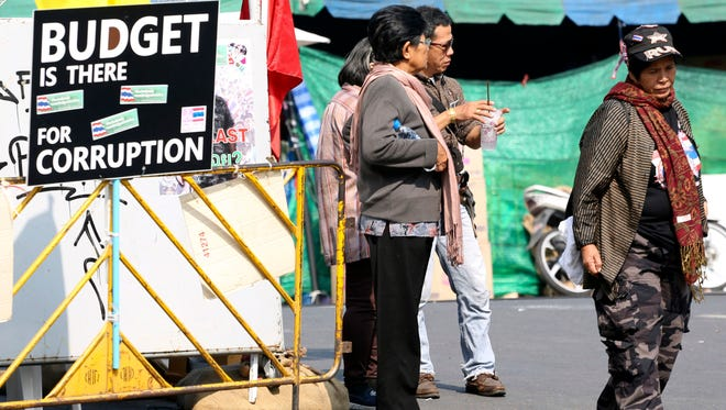 Thai anti-government protesters chat next to a protesting banner outside a makeshift camp where their colleagues were shot outside the Prime Minister's office in Bangkok on Dec. 28.