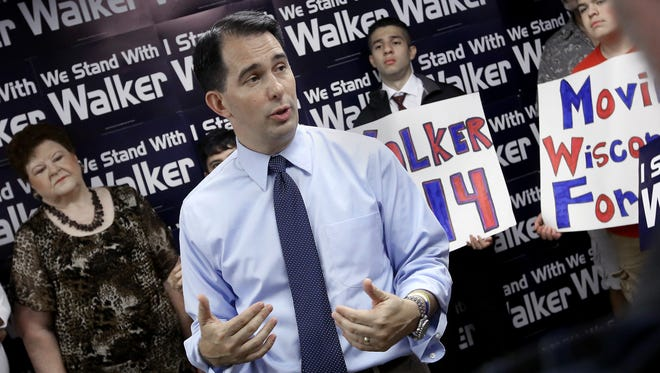 Wisconsin Gov. Scott Walker addresses members of the media and volunteers with the state's Republican Party during a stop at the party's Madison field office.