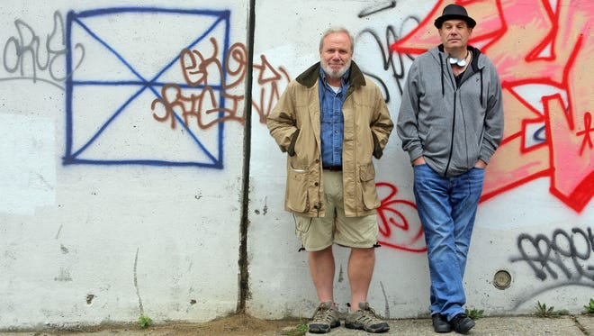 """Bill Zorzi, left, and David Simon, stand against a wall painted with temporary graffiti at the Schlobohm Houses public housing project in Yonkers Oct. 1, 2014. The Schlobohm Houses is one of the locations being used for filming of the HBO mini-series """"Show Me a Hero.""""  Zorsi is a writer and Simon is the producer of the film, which tells the story of the Yonkers desegregation crisis of the 1980s. The graffiti will be removed after filming is completed."""