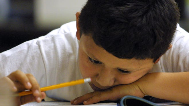 A young student in looks closely at a math exam.