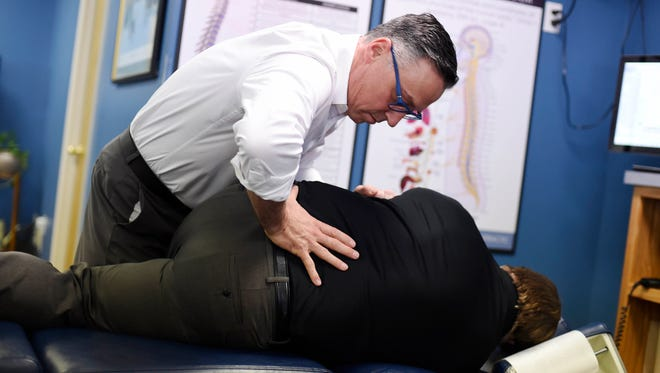 Dr. Kevin Jackson adjusts the back of Paul St. Clair of Newberry Township at Sigafoose-Jackson Chiropractic in Springettsbury Township.