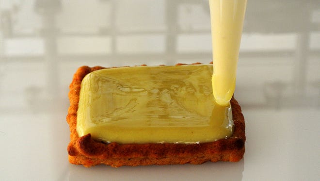 Cheese is added with a 3-D printer to the top of a black bean burger patty. Printers are being compared to microwaves' impact in the 1970s.