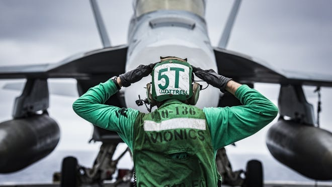 A Navy Electronics Technician signals to the crew of an EA-18G Growler on the flight deck of the USS Carl Vinson in June. The National Defense Authorization Act includes money for the study of how to quiet jet engines.
