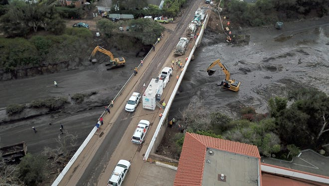Crews work to clear a mud and debris from U.S. Highway 101 in Montecito.