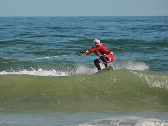 Surfing Santa being towed by a personal watercraft