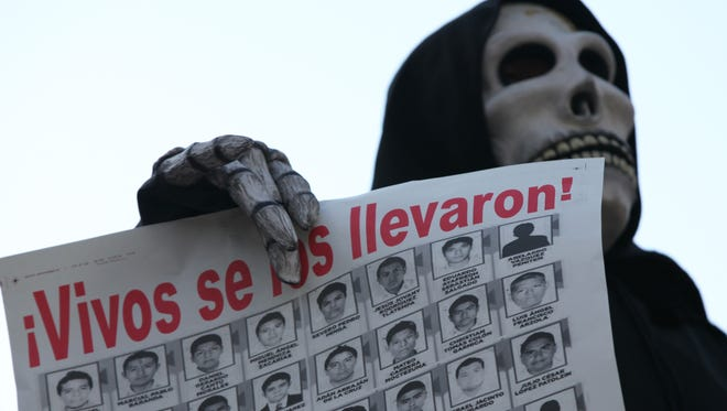 A man dressed as the Grim Reaper and carrying a poster with the photos of the missing participates in a march to protest the disappearance of 43 students in Mexico City on Nov. 16.
