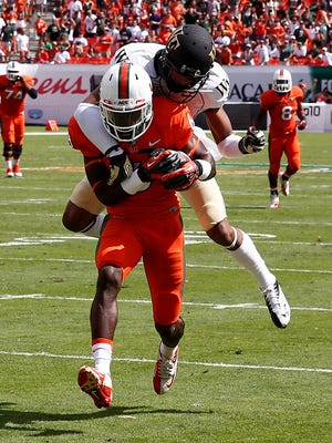 Miami Hurricanes wide receiver Herb Waters (6) catches a touchdown pass over Wake Forest Demon Deacons cornerback Kevin Johnson (9) in the second quarter at Sun Life Stadium.
