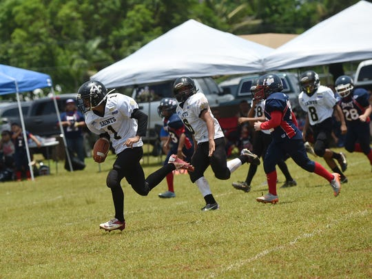 Saints player Raymon Sebastian (1) sprints toward the endzone against the Giants during their Triple J Ford GNYFF Youth Football game at Raiders Tiyan Field on Aug. 23.