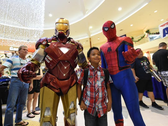 Spider-Man and Iron Man cosplayers pose for pictures