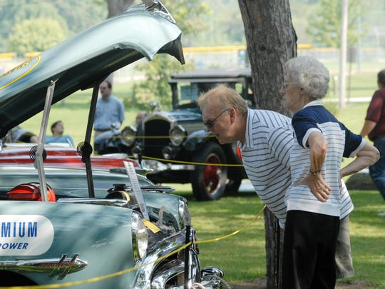 Mark Burk of Warren looks at the engine of a 1952 Hudson Hornet with his mother Ruth Burk also of Warren as they browse the cars on display Sunday morning during The Past and Its Wheels car show in Marysville Park. The show included original or restored cars older than 1959.