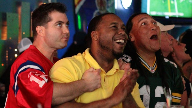 Seattle Seahawks fan Arnold Harper (center) claps as friend and Boston-native Wes Poirier reacts with a sudden disappointment after the Seahawks intercepted what would have been a New England Patriots touchdown in the end zone during the first half of Super Bowl XLIX on Sunday, February 1, 2015 while the game is televised at NYPD in downtown Palm Springs. At right is Palm Springs resident William Beyal who said he was rooting for the Seahawks because they beat his team, the Green Bay Packers, to advance to the Super Bowl.