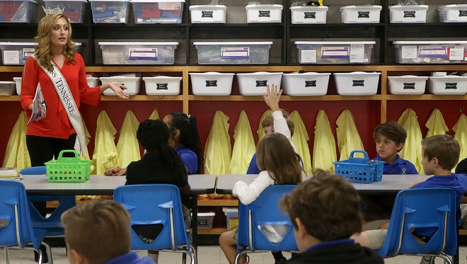 """Miss Tennessee Grace Burgess speaks with fourth-grade students in the STREAM lab at the Jackson Christian lower school in Jackson Wednesday. She read aloud """"If you keep your eyes open enough, oh, the stuff you will learn"""" from a Dr. Seuss book."""