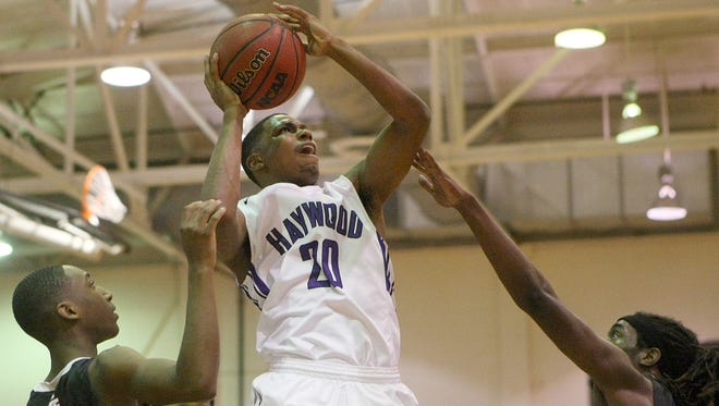 Haywood's Dedric Boyd (20) goes up for a shot between South Side's Geordan Reed, right, and Quaylon Fuller, left, at Haywood High School in Brownsville, Tenn., on Friday, Dec. 2, 2016. Reed fouled Boyd on the play.