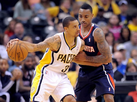 Indiana Pacers George Hill backs into the Atlanta Hawks' Jeff Teague (right) in the second half of their first game of the NBA playoffs  Sunday afternoon at Bankers Life Fieldhouse.