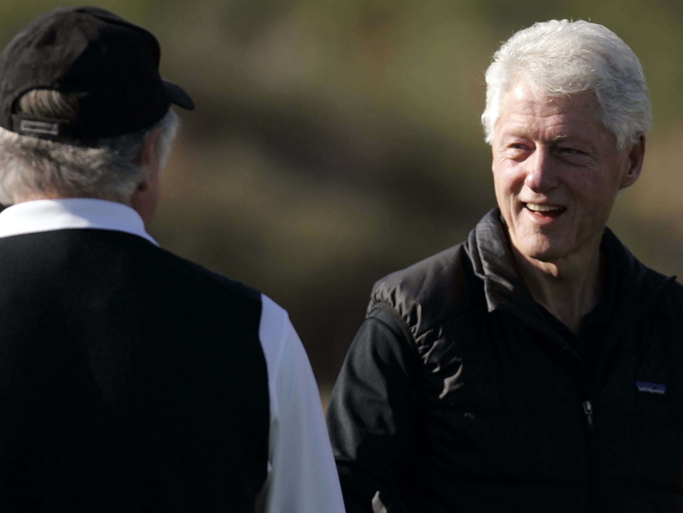 Former President Bill Clinton greets people on the