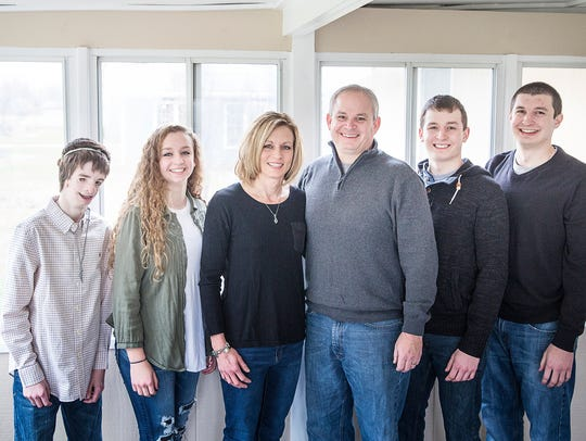 Grant Zgunda with his family at his home in Muncie