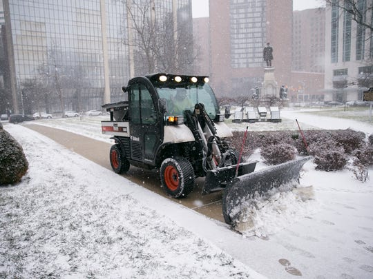 A plow clears grounds at the Indiana Statehouse on a snowy day that saw about a half inch of snow by mid-day, Indianapolis, Friday, Jan. 12, 2018.