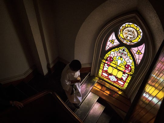 An altar server walks down from the choir loft after communion during Mass at San Carlos Borromeo Church in Carthage.