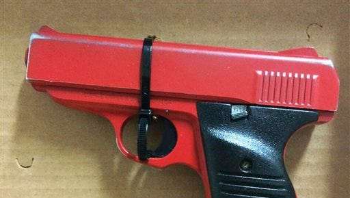 This photo provided by the Hamilton County Sheriff in Cincinnati shows a red-painted, 380-caliber handgun police found during the arrest of 23-year-old Orlando Lowery when responding to a call about a man with a gun. The arrest Friday came just four days after legislation was introduced in Ohio to require that lookalike guns be brightly colored or otherwise marked.