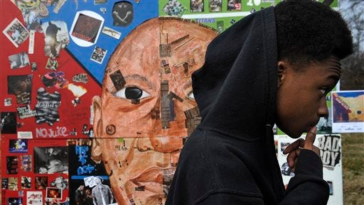 In this Dec. 20 photo, La Darious Barlow, 15, stands next to a mural he worked on with a group of artists in Nashville. The mural was completed in December as the first of three to be showcased at Nashville events in the next year. It debuts at a time of national dialogue about justice for young black men.