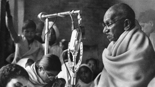 In a Jan. 22, 1948 file photo, Mohandas K. Gandhi squats before a microphone in New Delhi, India, to deliver prayer meeting discourse during second day of his fast to force communal peace in India. New England Brewing Co. in Connecticut is apologizing to Indians offended that the company is using Mohandas Gandhi's name and likeness on one of its beers. The brewery apologized on its Facebook page for the India pale ale it calls Gandhi-Bot. Critics in the U.S. and India have complained about the commercial use of Gandhi, revered for leading India to independence through nonviolence.