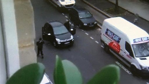 In this image made from amateur video recorded on Wednesday, Jan. 7, 2015 by Jordi Mir, masked gunman get into a car moments after shooting a police officer outside the offices of French satirical newspaper Charlie Hebdo in Paris. Paris residents captured chilling video images of two masked gunmen shooting a police officer after an attack at a French satirical newspaper. In the video, the gunmen armed with assault rifles are seen running up to an injured police officer, who lies squirming on the ground. The police officer raises his hands up before one of the assailants shoots him in the head at a close range. (AP Photo/Jordi Mir) NO SALES