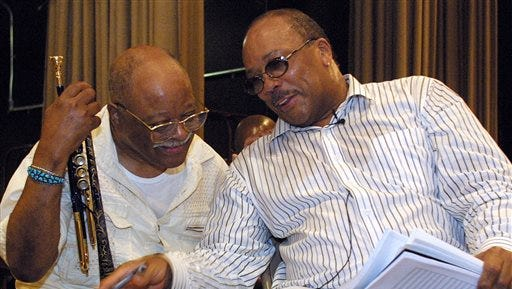 """This file photo shows Quincy Jones, right, talking with jazz musician Clark Terry at a rehearsal of """"Sonic Convergence,"""" in New York. Terry, a legendary jazz trumpeter, who mentored Miles Davis and Jones and played in the orchestras of both Count Basie and Duke Ellington and on """"The Tonight Show,"""" has died. He was 94."""