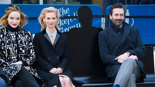 """Christina Hendricks, from left, January Jones and Jon Hamm appear at an unveiling of a bench dedicated to the """"Mad Men"""" series in front of the Time & Life Building on Monday, March 23, 2015 in New York. The bench shows a silhouette of Hamm's character Don Draper."""