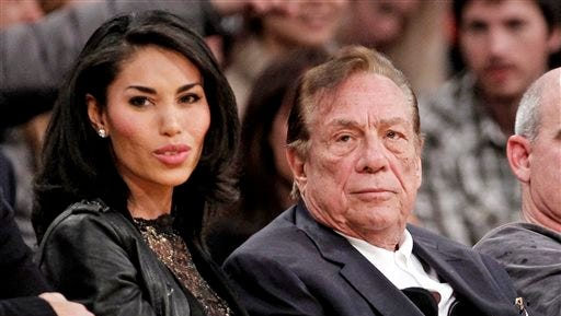 Los Angeles Clippers owner Donald Sterling, right, sits with V. Stiviano as they watch the Clippers play the Los Angeles Lakers on Dec. 19, 2011, during an NBA preseason basketball game in Los Angeles.