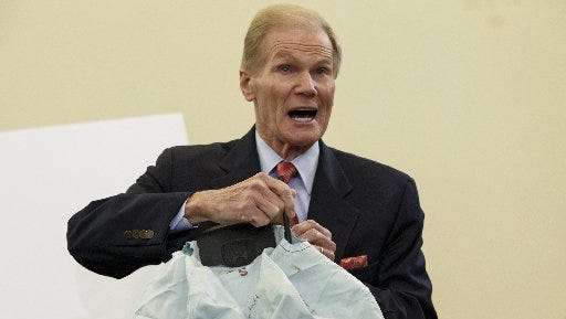 Senate Commerce Committee member Sen. Bill Nelson, D-Fla. displays on Nov. 20 the parts and function of a defective airbag made by Takata of Japan that has been linked to multiple deaths and injuries in cars driven in the U.S., during the committee's hearing on Capitol Hill in Washington.
