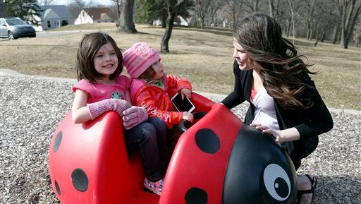 FILE - In this April 2, 2015, file photo, Michelle Halonen, enjoying the warm day with daughters Madilyn, left, and Ellie at a park in St. Louis Park, Minn., works full time at a gas station and still struggles to support her two young daughters. A new report on child welfare that found more U.S. children living in poverty than before the Great Recession belies the fanfare of the nation's economic turnaround.