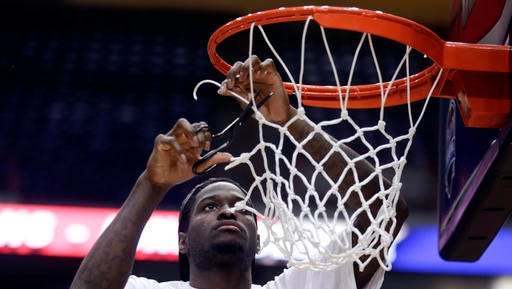 Iona guard A.J. English helps cut down the net after a 79-76 win over Monmouth in the Metro Atlantic Athletic Conference tournament final on  March 7 in Albany.