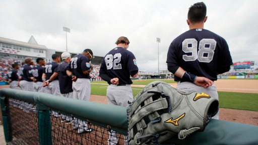 New York Yankees' Ben Gamel's glove sits at the top of the dugout fencing as Louis Torrens (98), Gamel (82) and the rest of the team stand during the playing of the national anthem before a spring training baseball game against the Minnesota Twins on Sunday, March 20, 2016, in Fort Myers, Fla.