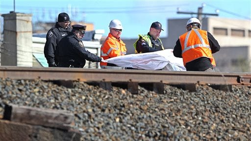 Police and investigators cover the body of one of the individuals killed in an Amtrak train crash in Chester, Pa., Sunday, April 3, 2016. The Amtrak train struck a piece of construction equipment just south of Philadelphia causing a derailment.