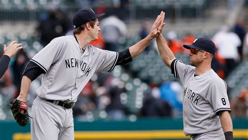 New York Yankees pitcher Andrew Miller, left, celebrates with left fielder Brett Gardner after a 8-4 win over the Detroit Tigers during a baseball game Saturday, April 9, 2016, in Detroit.
