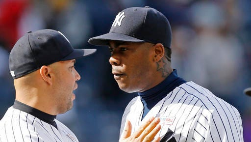 New York Yankees designated hitter Carlos Beltran, left, congratulates New York Yankees relief pitcher Aroldis Chapman after Chapman closed out the baseball game against the Chicago White Sox in New York, Sunday, May 15, 2016. Beltran hit his 400th career home run in the game and Chapman earned a save. The Yankees won 7-5.